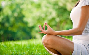 Woman sitting in the grass doing a yoga hand position.