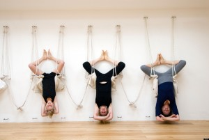 Image of three women hanging upside down performing a yoga pose on the Forward Motion Yoga website.