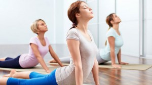 Three ladies in the cobra position at Forward Motion Yoga