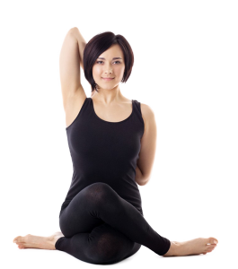 Photo of a woman sitting cross-legged with her arms touching behind her back on the Forward Motion Yoga website.