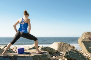 A woman doing yoga on some large rocks at the beach
