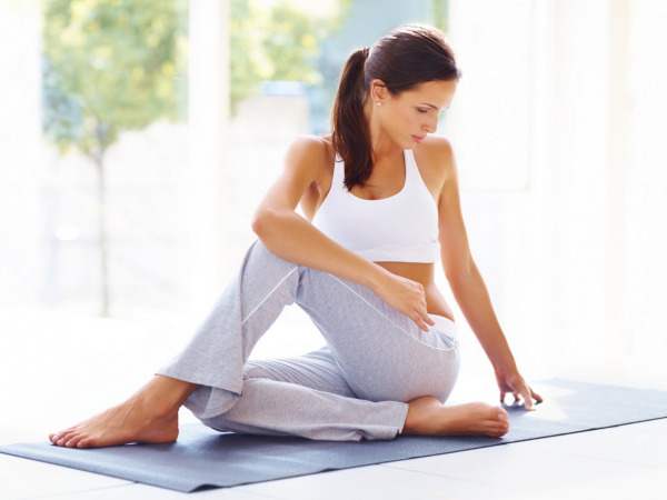 Woman in white top and grey pants doing a yoga pose on the Forward Motion Yoga website.
