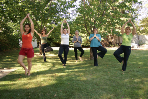 Students of Forward Motion Yoga holding the tree pose beneath some trees