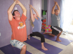 Two men and a woman doing yoga at Forward Motion Yoga