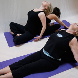 Four ladies doing yoga with each other at Forward Motion Yoga
