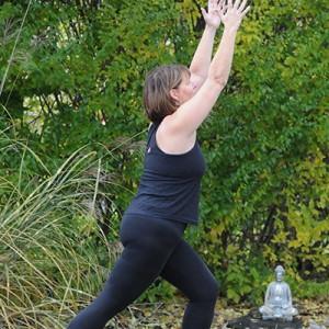 Marg Drudge doing yoga in a green garden