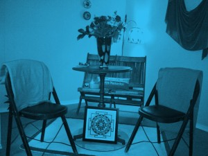 A blue-filtered photo of some seats and a table at Forward Motion Yoga