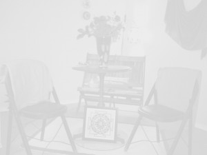 A near-opaque grayscale photo of some seats and a table at Forward Motion Yoga