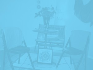 A near-opaque blue-filtered photo of some seats and a table at Forward Motion Yoga