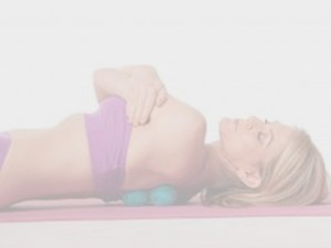 A lady lying down using her therapy balls