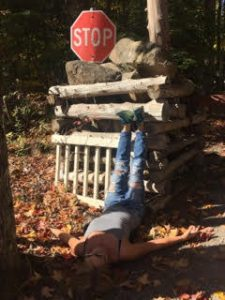 A photo a woman laying on the ground, with their feet resting on a pile of logs and rocks, with a stop sign behind the pile.