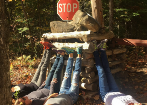 A photo of women laying on the ground, with their feet resting on a pile of logs and rocks, with a stop sign behind the pile.
