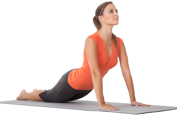 Lady in orange shirt and grey yoga pants in the cobra position at Forward Motion Yoga